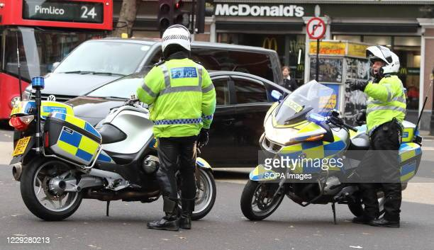 Two police traffic motorcycles about to put out cones to divert traffic as the demonstration march approaches. With a number of expected...