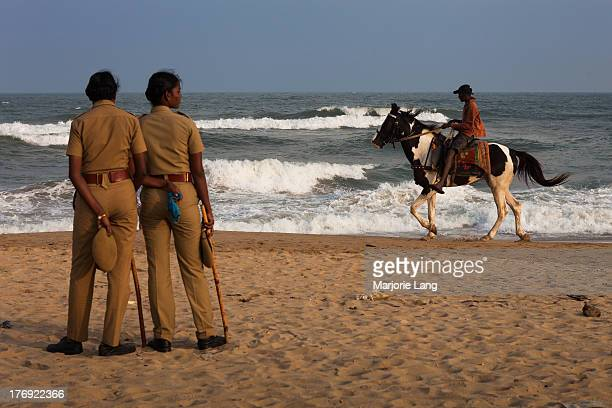 CONTENT] Two police women dressed in uniforms are watching the sea while a young boy is riding a horse in a late afternoon on Marina beach in Chennai...