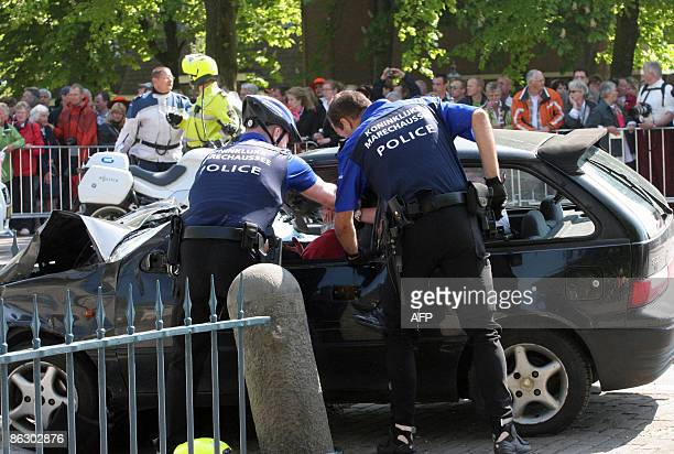 Two policemen attempt to stop the driver after he slammed with his car into Dutch festival-goers in Apeldoorn on April 30, 2009 killing five people...