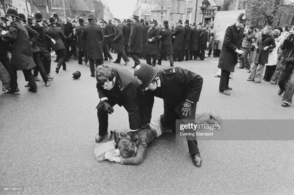 Two policemen blocking a men on the ground during a strike following the Grunwick Dispute, London, UK, 4th November 1977.