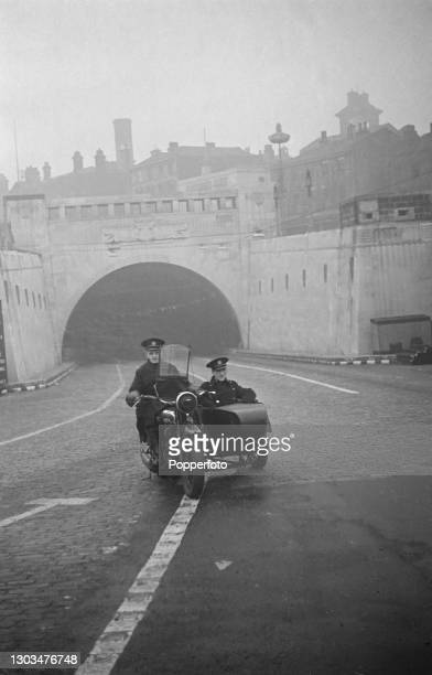 Two policemen from the Mersey Tunnels Police ride out from the Mersey Queensway Tunnel on a motorcycle and sidecar in Liverpool, England during World...