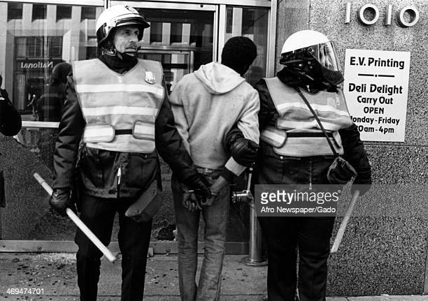 Two policemen in riot gear arresting a young man near Vermont Avenue NW one of 38 people arrested for looting and disorderly conduct Washington DC...