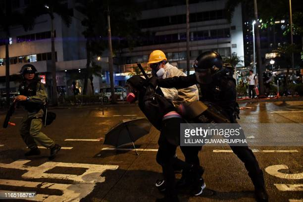 TOPSHOT Two policemen including one disguised as a protester detain a protester on Hennessy Road in Hong Kong on August 31 in the latest opposition...