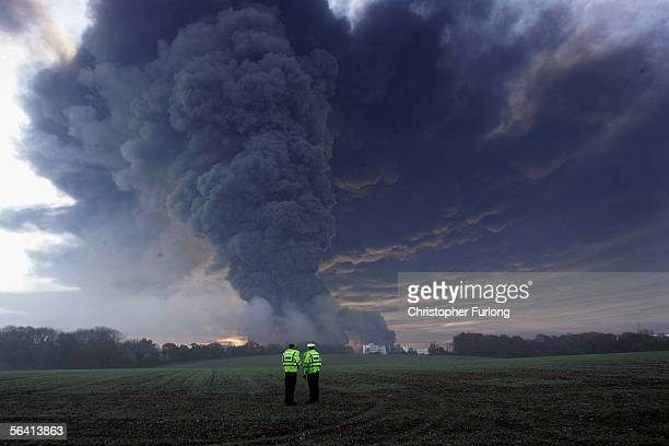 Two policemen look on as plumes of smoke rise from Bruncefield oil depot on December 11 2005 in Hemel Hempstead EnglandThe explosions are being...