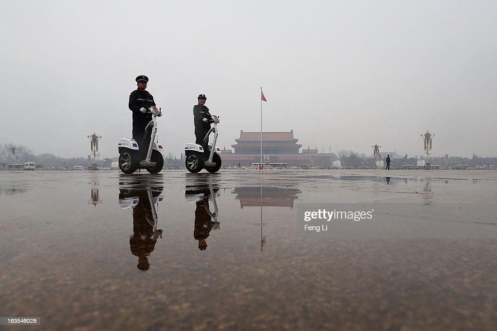 Two policemen ride two-wheel electronic vehicles patrol on the Tiananmen Square during the closing session of the annual Chinese People's Political Consultative Conference (CPPCC) on March 12, 2013 in Beijing, China. The newly-elected Chairman of the CPPCC Yu Zhengsheng pledged Tuesday that China will not copy Western political systems under any circumstances.