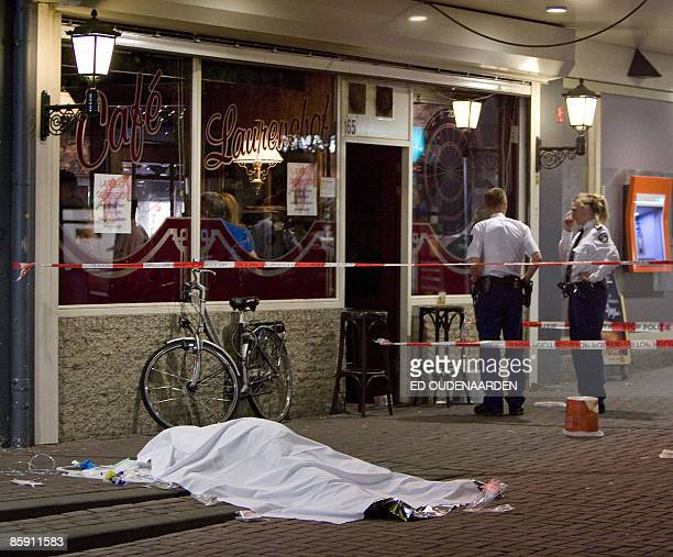 Two policemen stand in front of a dead man covered by a white blanket as he lays on the floor after a man pulled a gun and opened fire in a crowded...