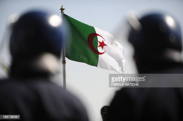 Two policemen stands as the Algerian national flag flies during a march of thousands of auxiliary police near the Parliament in Algiers on March 7...