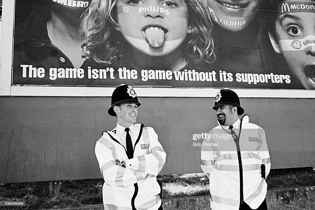 Two policemen talking to each other under a large billboard advert before the start of the England v Scotland UEFA European Championships group match played at Wembley stadium, London on the 15th June 1996. England won the match 2-0.