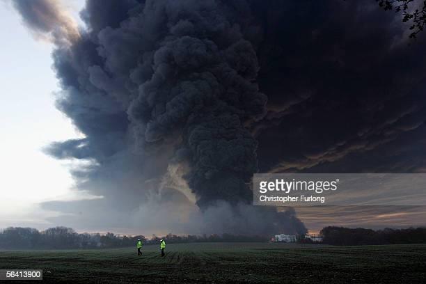 Two policemen walk in field as plumes of smoke rise from Bruncefield oil depot on December 11 2005 in Hemel Hempstead EnglandThe explosions are being...