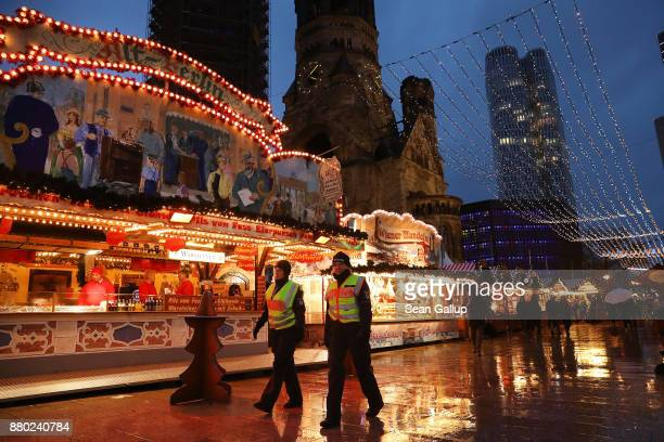 Two policewomen walk among stalls at the annual Christmas market on its opening day at Breitscheidplatz where a year ago 11 people were killed in a...