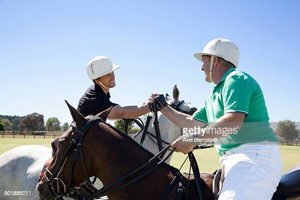 Two polo players shaking hands