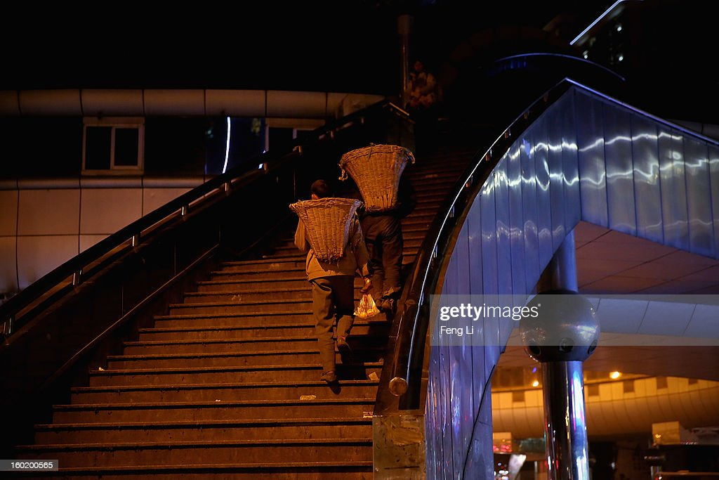 Two poor men carrying the bamboo baskets walk onto a overpass on January 27, 2013 in Guiyang of Guizhou Province, China.