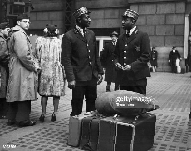 Two porters or 'redcaps' pause to chat during their shift at the Pennsylvania Railroad Station