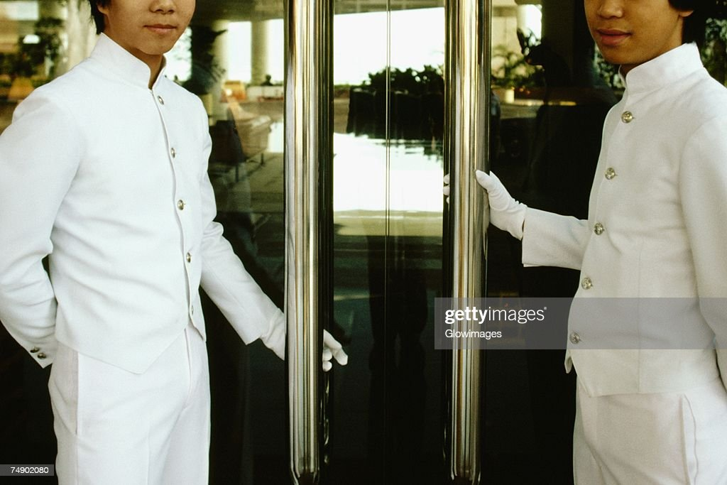 Two porters standing at the entrance of a hotel doors, Regent Hotel, Kowloon, Hong Kong, China : Foto de stock
