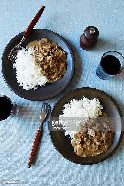 Two portions of beef stroganoff with rice