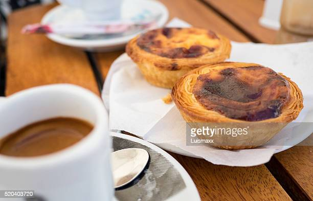 Two portuguese custard tarts on a cafe table
