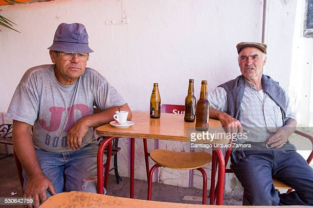Two Portuguese male adults relaxed having a beer at a bar in the small town of Baiona, Alentejo, Portugal. Adult men usually gather together to chat...