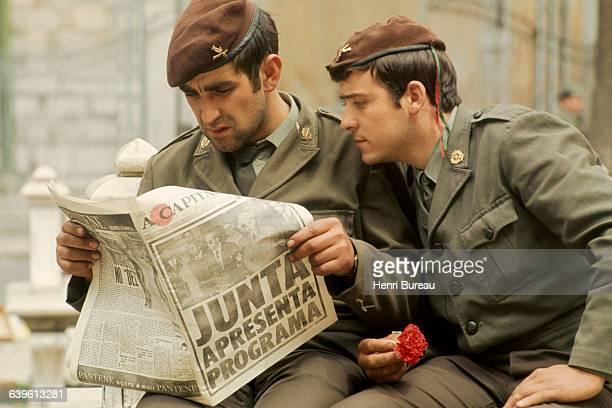 Two Portuguese soldiers reading a newspaper to find out the latest on the Carnation Revolution in Portugal