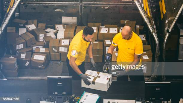 two postal warehouse workers scanning a package - post structure stock pictures, royalty-free photos & images