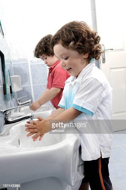 Two preschool aged children washing their hands