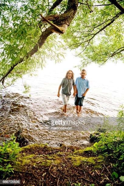 """two preteen brothers dipping their feets in lake. - """"martine doucet"""" or martinedoucet stock pictures, royalty-free photos & images"""