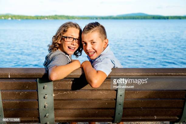 Two preteen brothers sitting on bench in front of lake.