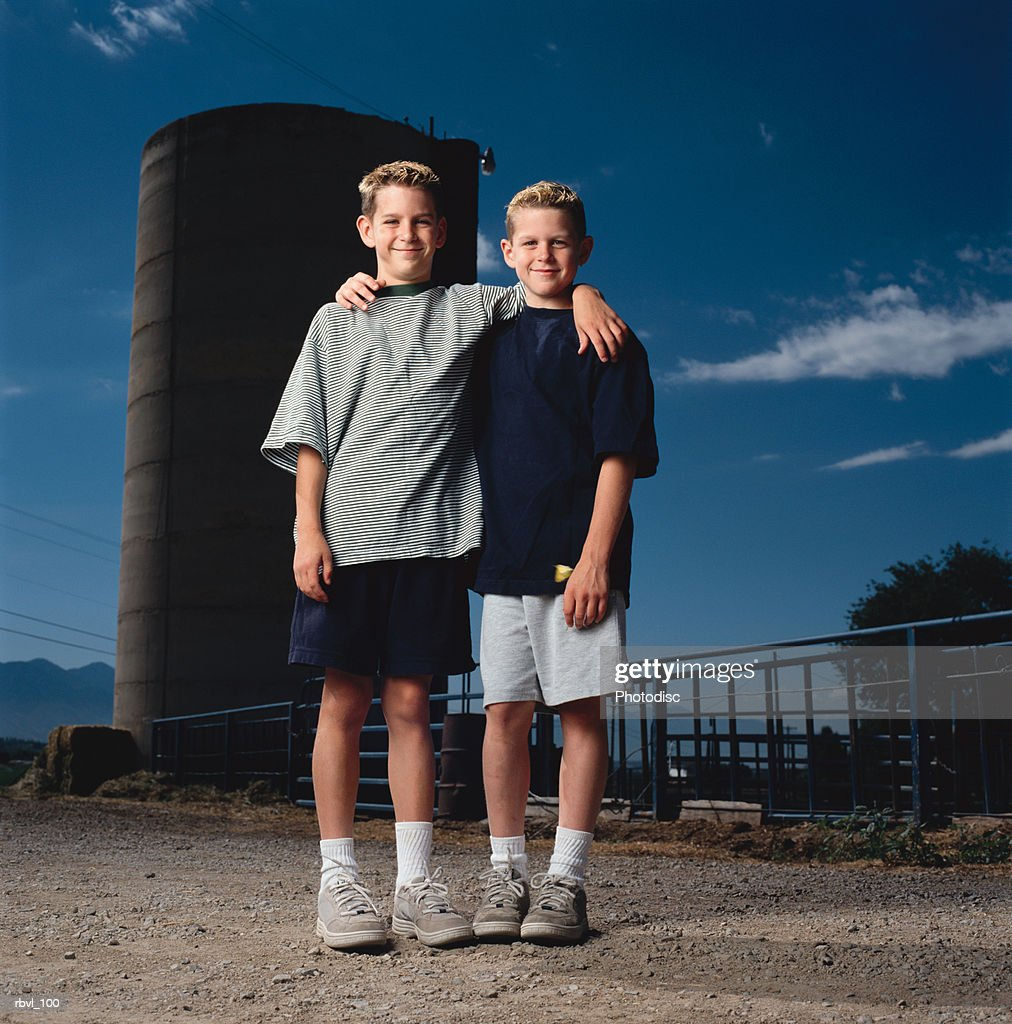 two preteen caucasian boys in shorts and t-shirts standing outdoors with their arm around each others shoulder smiling : Foto de stock