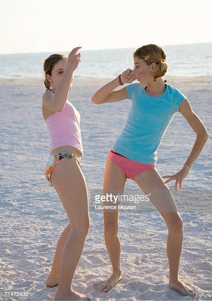 two preteen girls dancing on beach - one piece swimsuit stock pictures, royalty-free photos & images