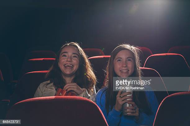 Two Pre-Teen girls in movie theater watching a movie