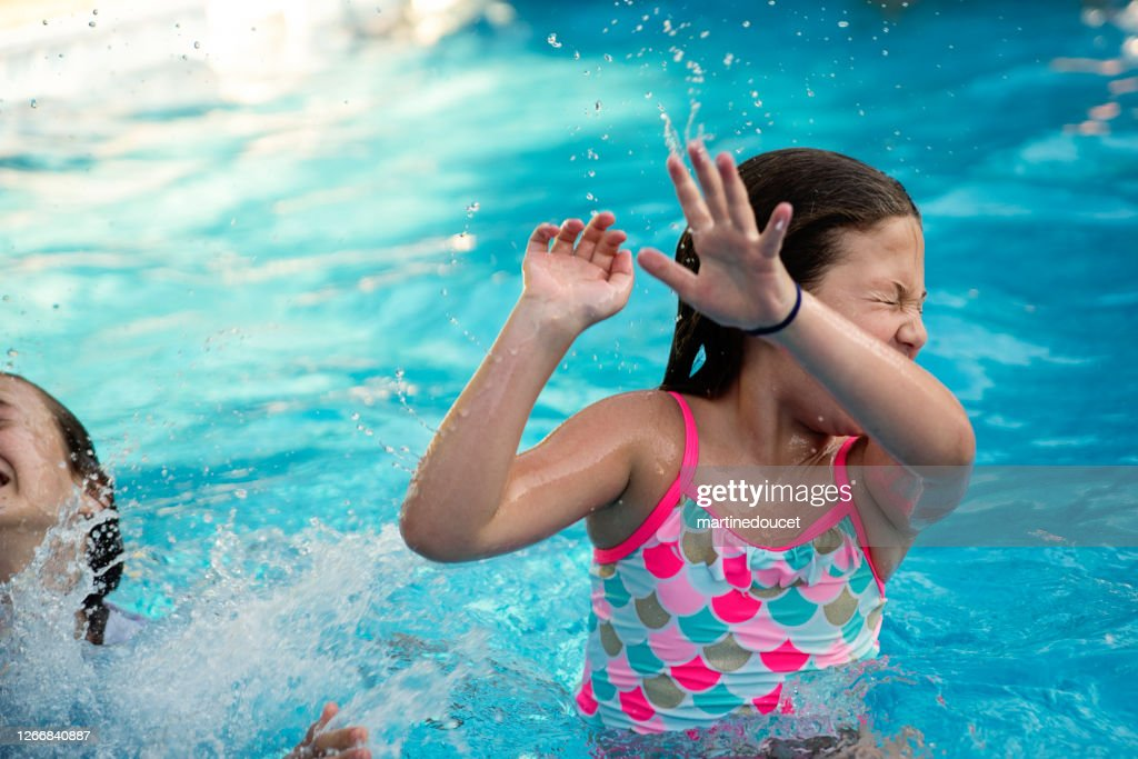 Two preteen girls in pool playing and making faces. : Stock Photo