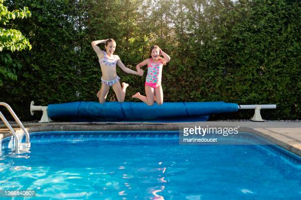 """two preteen girls jumping in pool making faces. - """"martine doucet"""" or martinedoucet stock pictures, royalty-free photos & images"""