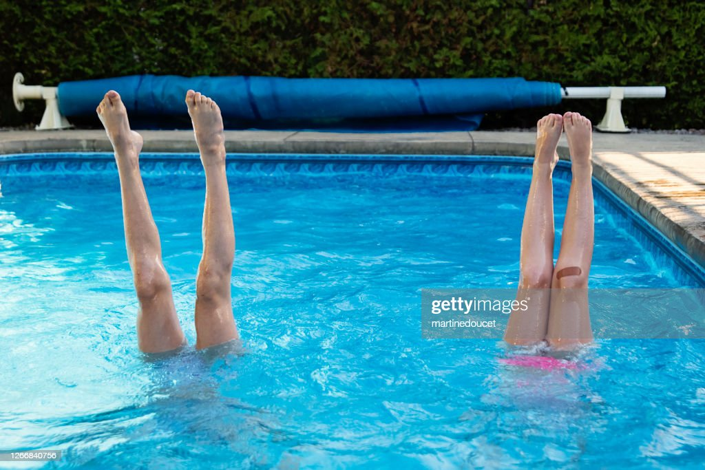 Two preteen girl's legs standing up in pool. : Stock Photo