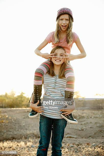 Two preteen girls one on the others shoulders.