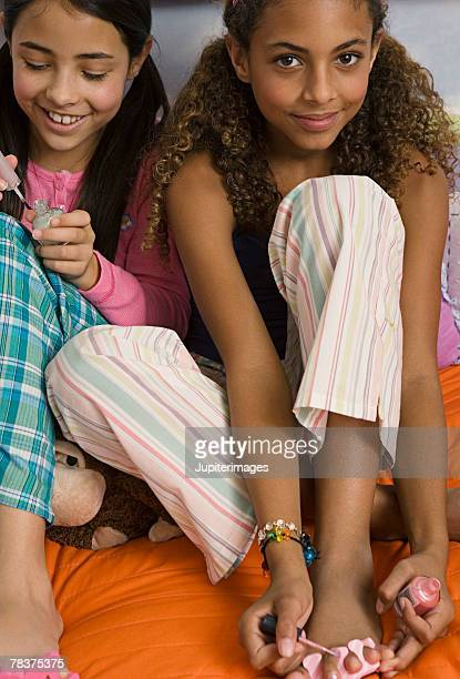 Two preteen girls painting toenails