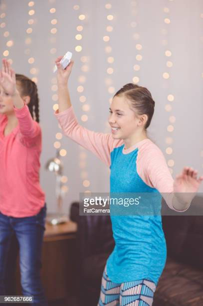 Two pre-teen girls play a virtual dancing game together