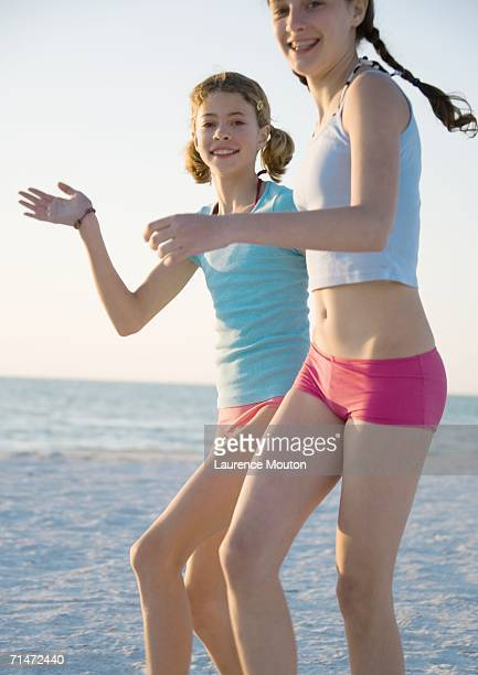 two preteen girls running on beach - one piece swimsuit stock pictures, royalty-free photos & images