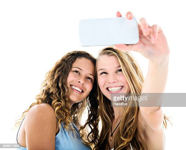 Two pretty women smile, taking a selfie.