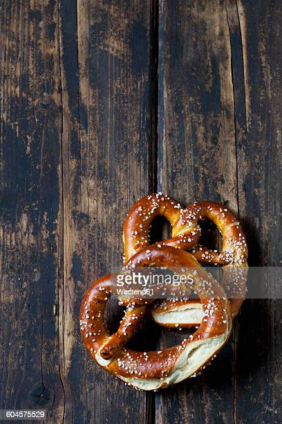 Two pretzels on dark wood