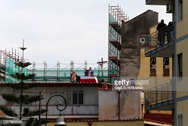 Two priests celebrate Sunday Mass from the roof of their church the Santa Maria della Salute in the city of Naples on March 22 2020 Italian Prime...