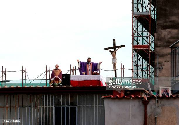 Two priests celebrate the Sunday Holy Mass from the roof of their church Santa Maria della Salute in Naples on March 222020 Italian Prime Minister...