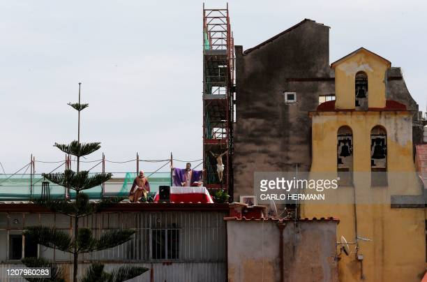Two priests celebrate the Sunday Mass from the roof of their church Santa Maria della Salute in Naples on March 22 2020 Italian Prime Minister...