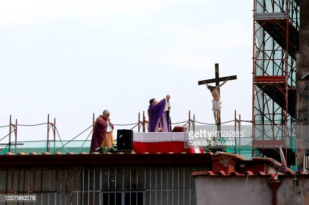 Two priests celebrate the Sunday Mass from the roof of their Santa Maria della Salute church in the city of Naples on March 22 2020 Italian Prime...
