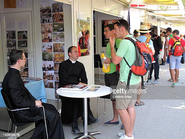 Two priests reporting on his religious order to young pilgrims Vocations Fair organized in Madrid's Retiro Park in the World Youth Day celebrated by...