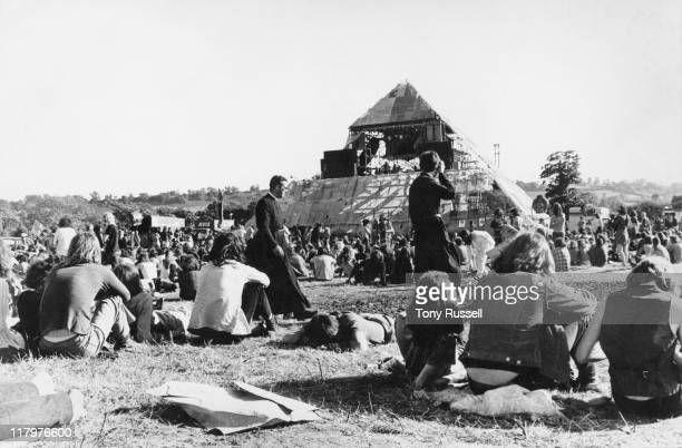Two priests walking amonmg the crowds of festival-goers pictured from behind looking toward the Pyramid stage at the Glastonbury Festival, at Worthy...