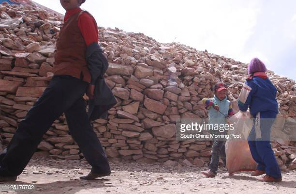 Two primary pupils pick up trash at Gyanag Mani Wall, the largest mani stone wall in the world, in Jiegu, Yushu, Qinghai, April 11, 2011. A...
