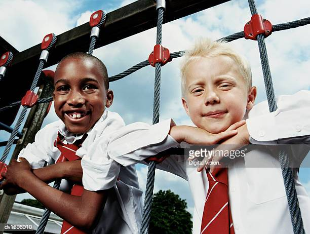 Two Primary School Boys Lean on a Climbing Frame and Smile at the Camera