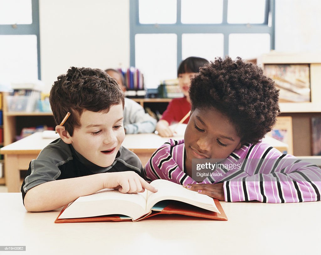 Two Primary Schoolboys Looking at a Textbook in a Classroom : Stock Photo