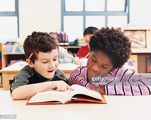 Two Primary Schoolboys Looking at a Textbook in a Classroom