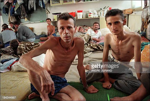 Two prisoners sit on the ground during a visit of journalists and members of the Red Cross 13 August 1992 in Serb camp in Tjernopolje near Prijedor...