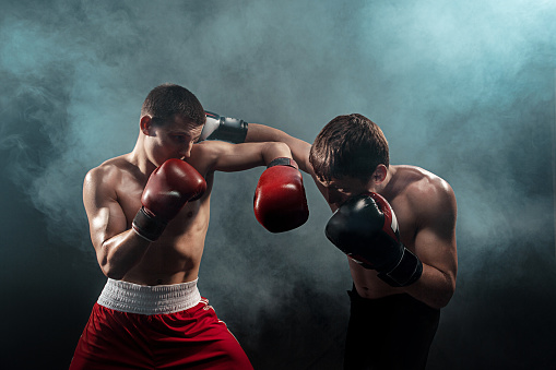 Two professional boxer boxing on black smoky background 813192598